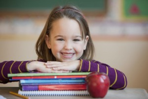 Caucasian girl sitting at school desk with books and apple