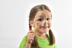 Little Girl Looks Through Magnification Glas